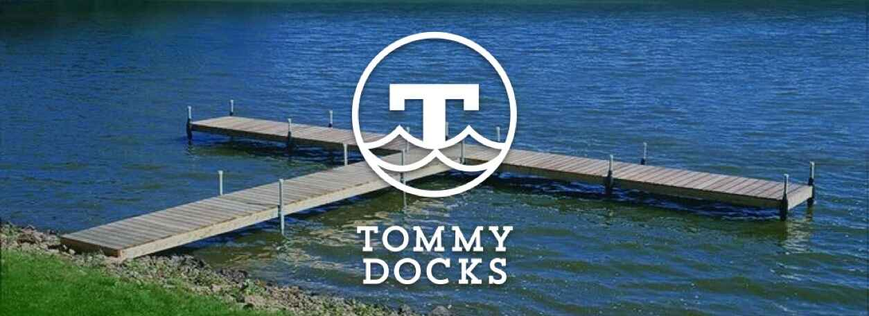 Tommy Docks logo with dock in background on lake